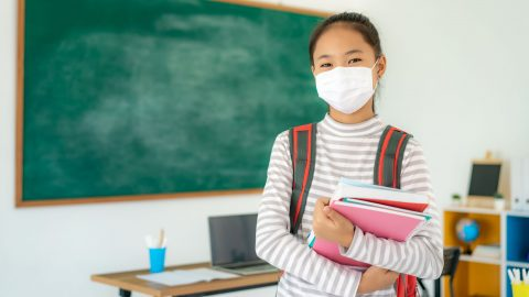Young Masked Oriental Girl in a School Room