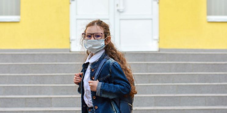 Young Masked Girl in Front of School Steps