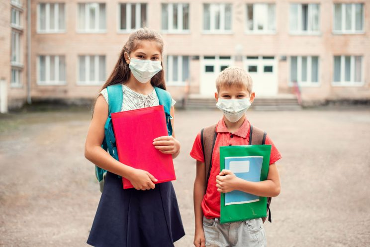 Young Brother and Sister Masked in a School Courtyard